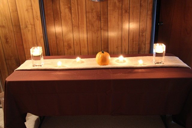 Pumpkins on the ends votive candles and a floating candle in the middle